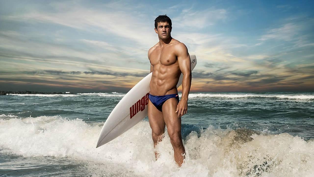 Muscular Hunk in a Blue Bikini with a Surfboard