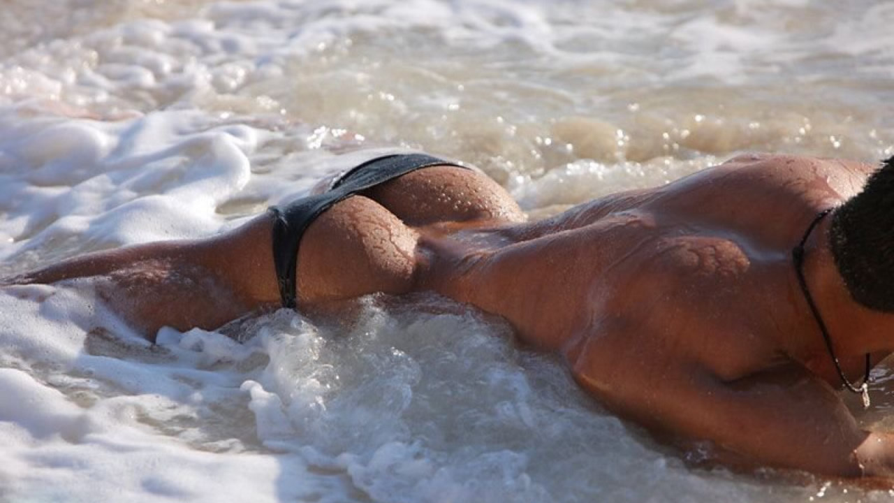 Ass in Little Black Speedo at the Edge of the Ocean