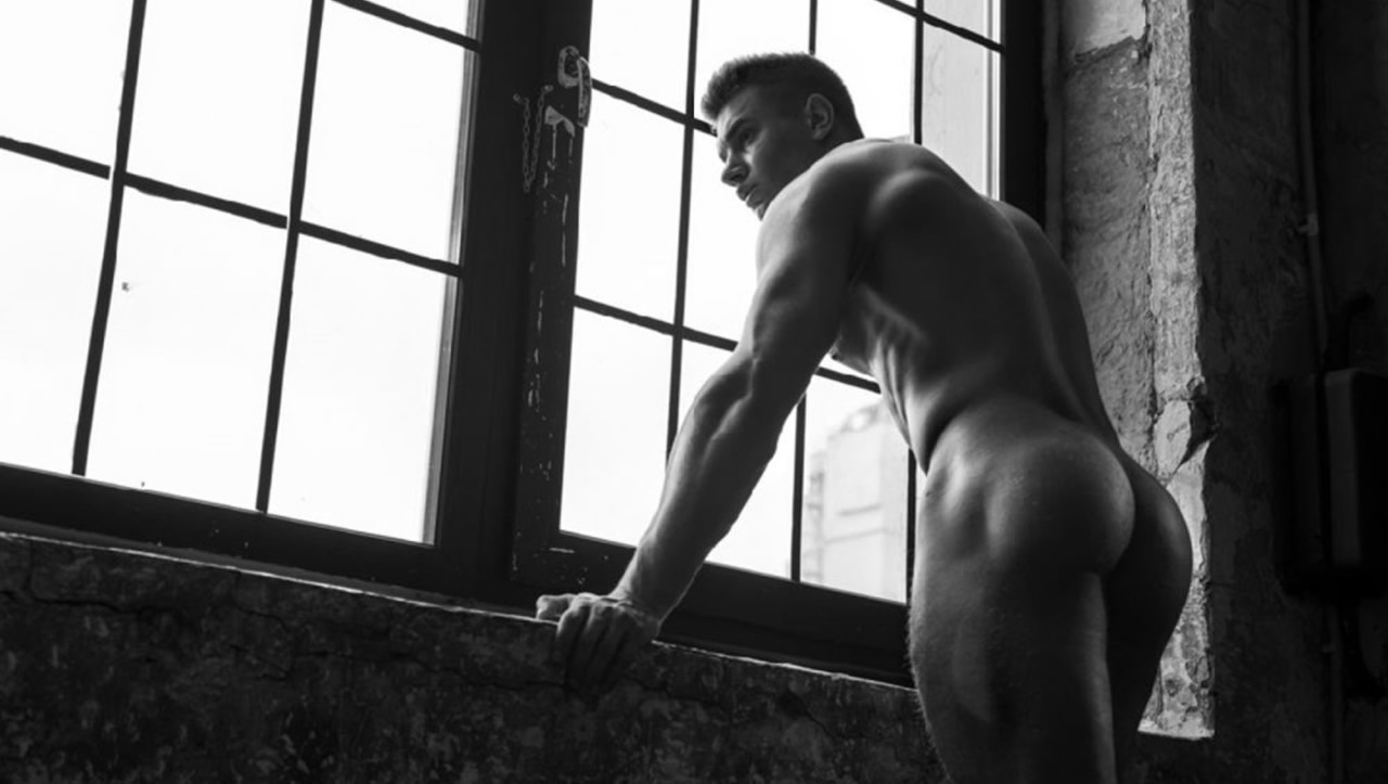 Black and White Rearview Muscular Stud Standing at a Window