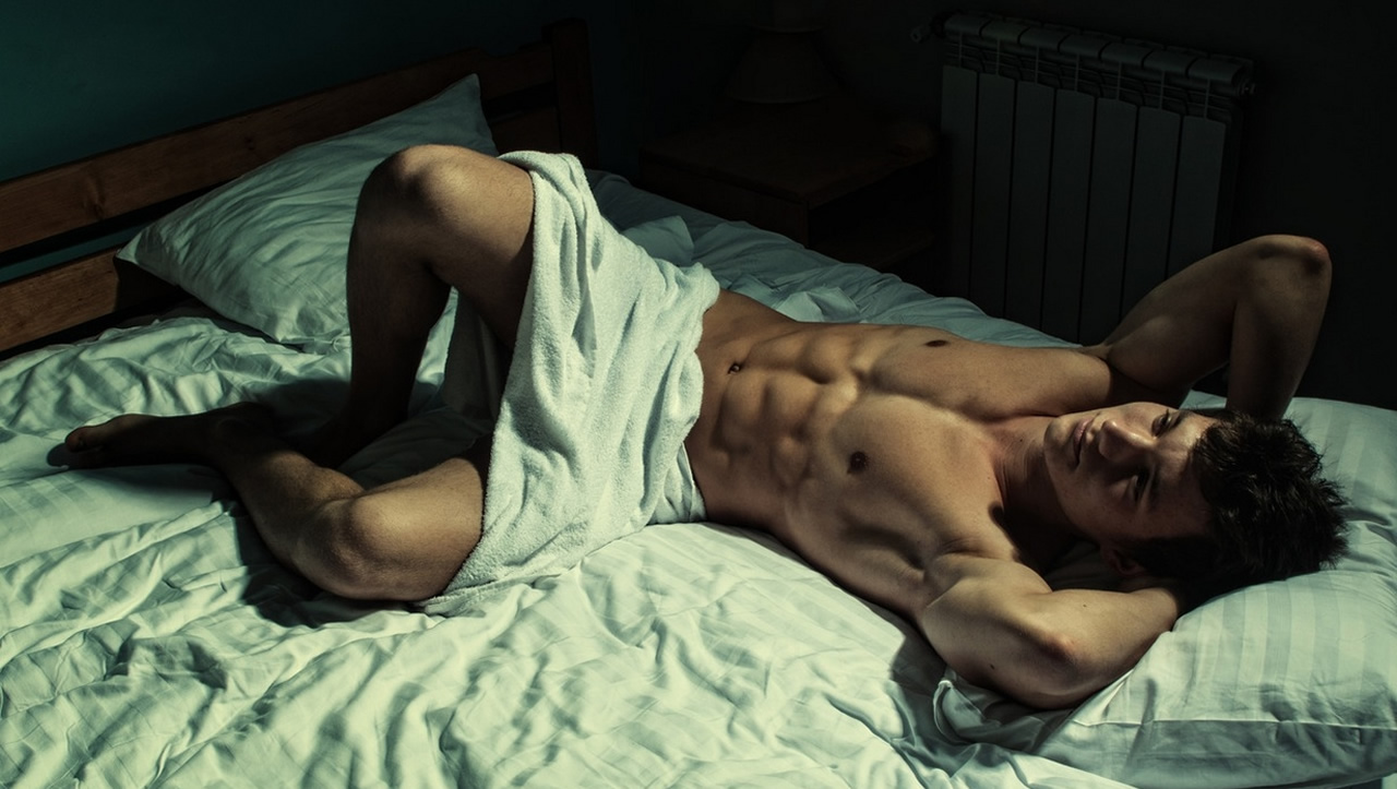 Ripped Stud in a Towel on a Bed