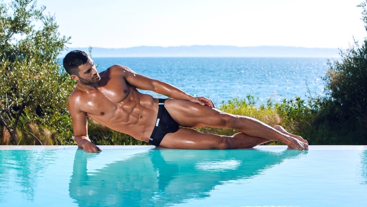 Muscular Hunk in a Navy Blue Bikini at the Edge of an Infinity Pool
