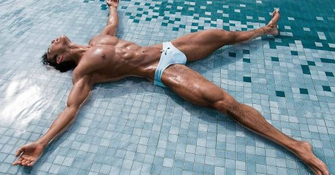 Ripped Young Guy in Light Blue Bikini at the Edge of a Pool
