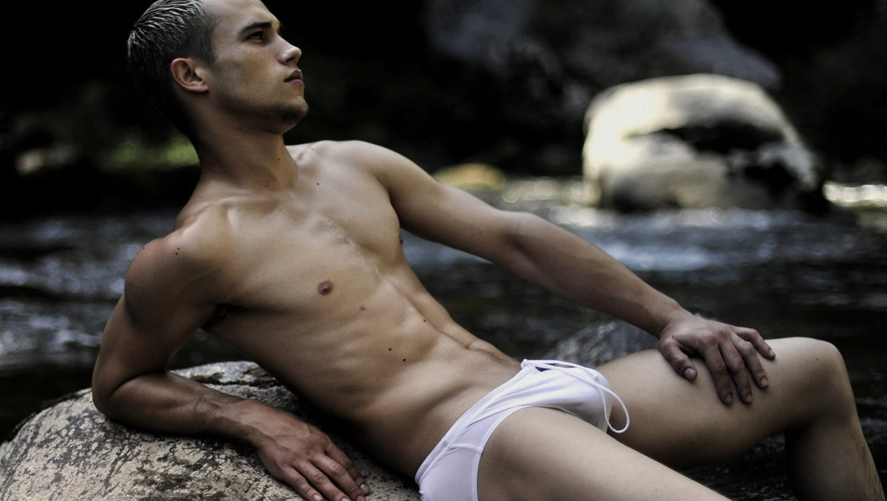 Fit Young Guy in a White Bikini on a Rock at the Waters Edge