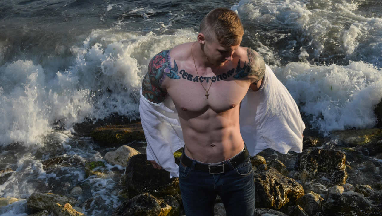 Tattooed Jock in Jeans Taking Off His Shirt on the Rocks