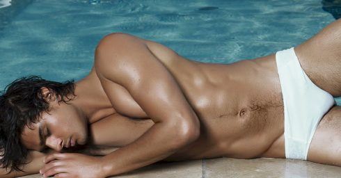 Fit Young Guy in a White Bikini at the Edge of a Pool