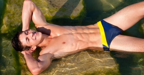 Ripped Young Guy in a Blue and Yellow Bikini in a Shallow Pond