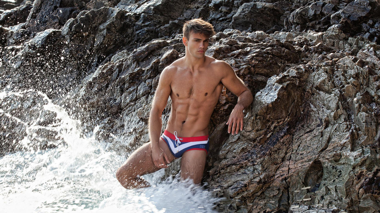 Athletic Young Guy on the Rocks at the Edge of the Ocean