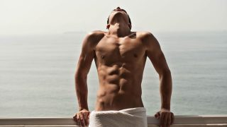 Fit Guy in a Towel on a Deck Overlooking the Ocean